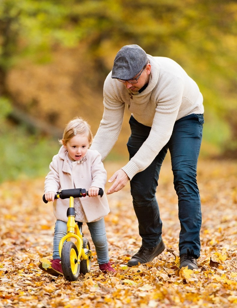 Young father with his little daughter with bicycle outside in autumn nature.