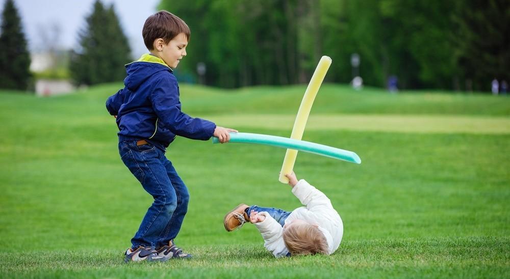 Preschool boys fighting with toy swords